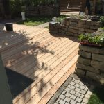 Holzterrasse mit Natursteinmauer